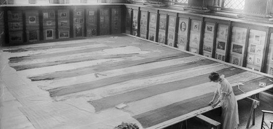 A conservator works on the Star-Spangled Banner in 1914